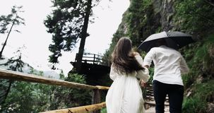 Young couple in the romantic trip running from the wooden bridge in the middle of amazing landscape with big mountains.  stock video footage