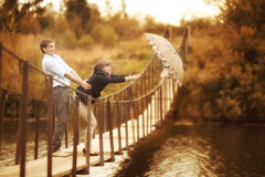 Young couple on a rope bridge. Under the umbrella Royalty Free Stock Photos