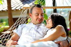 Young couple on a rope hammock in a cottage front view Royalty Free Stock Photography