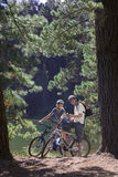 Young couple, with rucksacks, mountain biking along woodland trail beside lake, holding map, smiling, portrait stock photos