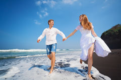 Young couple run by black sand beach along sea surf. Happy family on honeymoon holiday - just married young men and women run with fun by black sand beach along Stock Photography