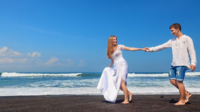 Young couple run by black sand beach along sea surf. Happy family on honeymoon holiday - just married young men and women run with fun by black sand beach along stock image