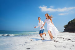 Young couple run by black sand beach along sea surf. Happy newlywed family on honeymoon holiday - just married loving couple run with fun by black sand beach Stock Images