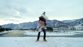 Young couple runing in mountains in winter. At sunset. Slow motion stock video footage