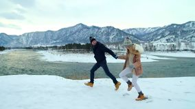 Young couple runing in winter mountains. Young couple runing in mountains in winter at sunset. Slow motion stock footage