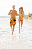 Young couple running along the beach. Young cheerful couple running along the beach Royalty Free Stock Images