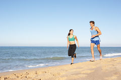 Young Couple  Running Along Beach. Young Couple In Fitness Clothing Running Along Beach Stock Photography