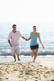 Young Couple Running Along Beach On Holiday Stock Photo