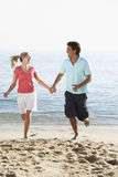 Young Couple Running Along Beach On Holiday Royalty Free Stock Photography
