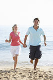 Young Couple Running Along Beach On Holiday Royalty Free Stock Photos
