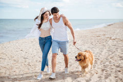 Young couple running along the beach with their dog Royalty Free Stock Image