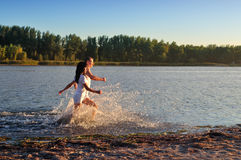 Young couple running along the river Stock Photography