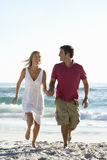Young Couple Running Along Sandy Beach On Holiday Stock Photography