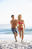 Young Couple Running Along Sandy Beach on Holiday Stock Images