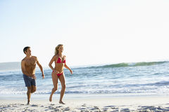 Young Couple Running Along Sandy Beach on Holiday Stock Photo