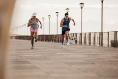 Young couple running along a seaside promenade. Healthy young runners sprinting outdoors in morning stock photo