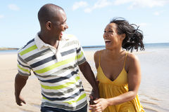 Young Couple Running Along Shoreline Holding H Royalty Free Stock Photo