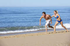 Young Couple Running Along Summer Beach Stock Photos