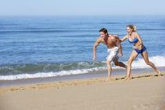 Young Couple Running Along Summer Beach Stock Photos
