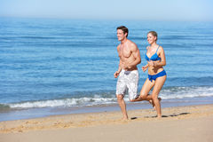Young Couple Running Along Summer Beach Stock Photo