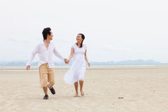 Young Couple Running Along Winter Beach Stock Photo
