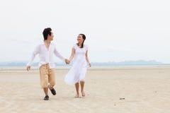 Young Couple Running Along Winter Beach Stock Photo