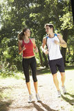 Young Couple Running Along Woodland Path Royalty Free Stock Images