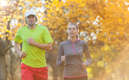 Young couple running in autumn season Stock Photos