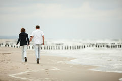 Young couple running on beach Stock Photos
