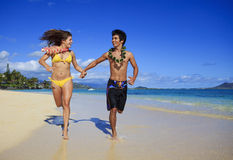 Young couple running on the beach Royalty Free Stock Images