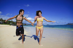 Young couple running on the beach Royalty Free Stock Image