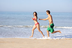 Young couple running on beach. In the sun royalty free stock photography