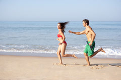 Young couple running on beach. In the sun royalty free stock images