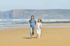 Young couple running at the beach. Young couple in love running at the beach Stock Photo