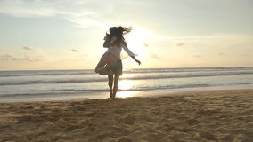 Young couple is running on the beach, man hug and spin around his woman on sunset. Girl jumps into her boyfriend arms