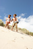 Young Couple Running Down Sand Dune. On Beach Royalty Free Stock Images