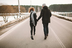 Young couple running on the empty road holding hands Royalty Free Stock Photography