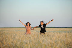 Young couple running in a field Royalty Free Stock Photos