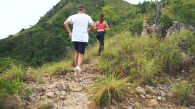 Young couple running on mountain trail. stock video footage