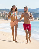 Young couple running near the sea stock image