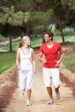 Young couple running in park. Smiling Stock Photo