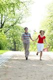 Young couple running in park. Holding hands Stock Photos