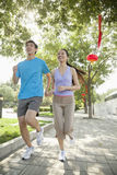 A Young Couple Running in Park Stock Image