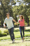 Young Couple Running Through Park Royalty Free Stock Images