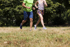 Young couple running in the park on a sunny day Stock Photo