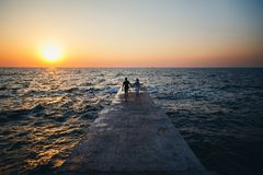 Young couple running at the pier towards the sunrise sun at the beach summer time royalty free stock photo