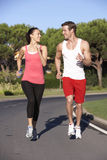 Young Couple Running On Road Stock Photos
