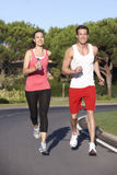 Young Couple Running On Road Royalty Free Stock Image