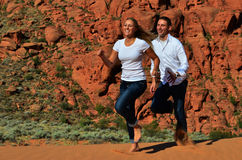 Young Couple Running on a Sand Dune Stock Images