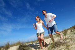 Young couple running on sandy beach Royalty Free Stock Image